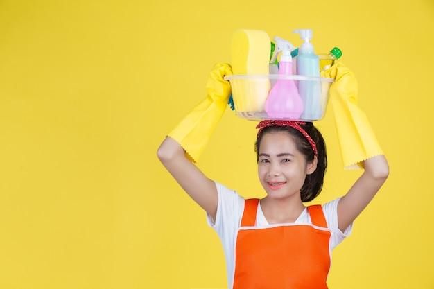 Nettoyage . une belle femme avec un appareil de nettoyage sur un jaune. Photo gratuit