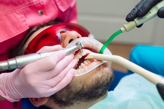 Nettoyage professionnel des dents, dentiste nettoie les dents d'un patient. Photo Premium