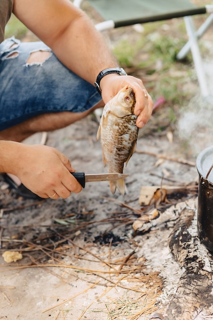 Nettoyer et trancher le poisson pour le bouillon de poisson dans la nature près du feu Photo Premium
