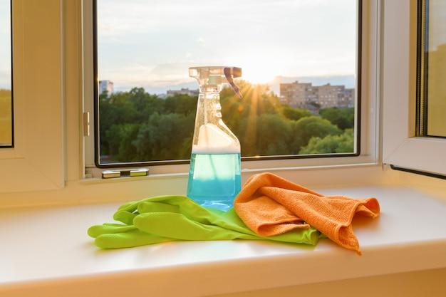 Nettoyer les vitres des gants de protection en caoutchouc, du chiffon et du détergent pour pulvérisateur. Photo Premium