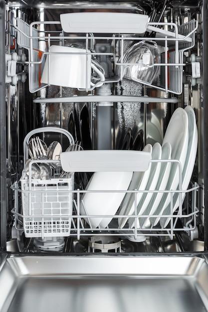 Nettoyez les assiettes, les tasses, les verres et les couverts au lave-vaisselle après Photo Premium
