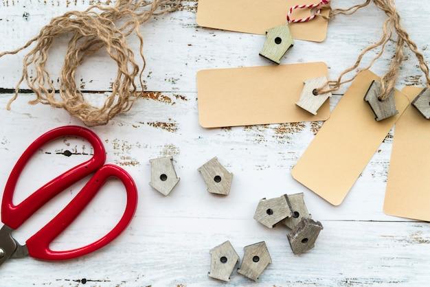 Nichoirs d'oiseaux miniatures; mots clés; ficelle et ciseaux sur un bureau blanc Photo gratuit