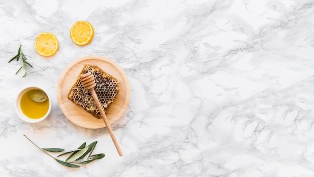 Nid d'abeille avec de l'huile d'olive sur fond de marbre blanc Photo gratuit