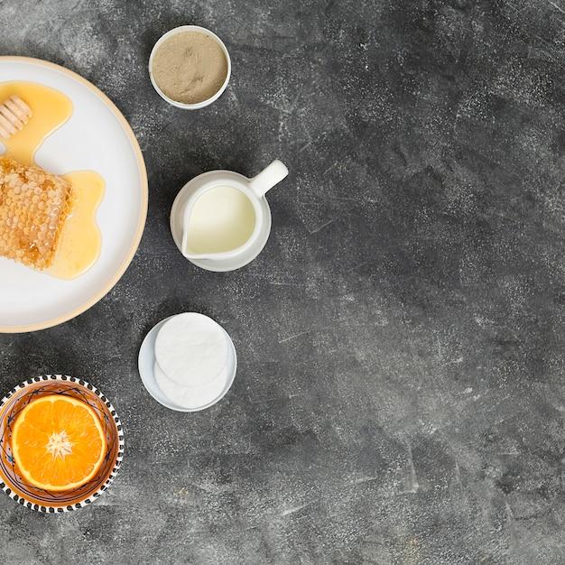 Nid d'abeille sur plaque en céramique avec orange coupée en deux; des tampons de coton; pichet de lait et d'argile de rhassoul sur fond de béton noir Photo gratuit