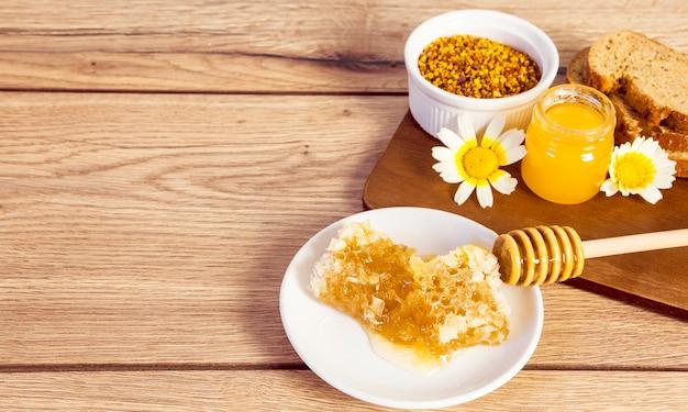 Nid d'abeille; pollen d'abeille; miel et pain tranches sur une surface en bois Photo gratuit