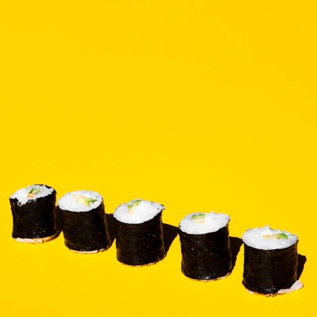 Nigiri roule sur un fond jaune Photo gratuit