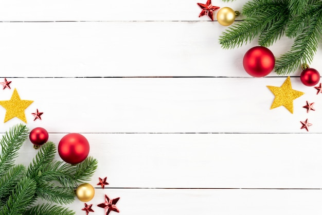 Noël avec des branches d'épinette, boule rouge et étoile sur fond en bois. Photo Premium