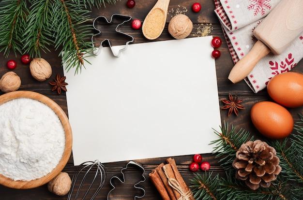 Noël ingrédients de cuisson, biscuits, épices, baies, œufs et farine sur bois sombre Photo Premium