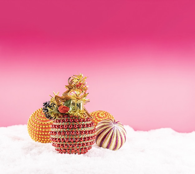 Noël Avec Des Jouets Colorés Sur La Neige Sur Fond Rose Photo gratuit