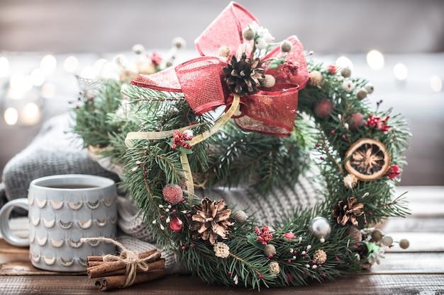 Noël Nature Morte D'arbres Et De Décorations, Couronne Festive Sur Fond De Vêtements Tricotés Et De Belles Tasses Photo Premium