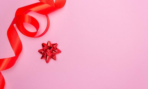 Noeud Cadeau Rouge Sur Fond Rose Et Ruban De Satin Rouge Sur Le Côté Photo Premium