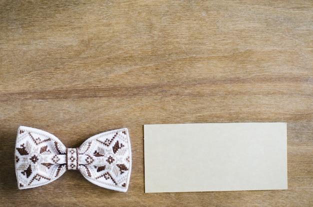 Noeud papillon et carte vide sur fond en bois. Photo Premium