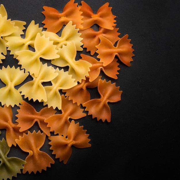 Noeud papillon italien coloré pâtes fraîches sur fond noir Photo gratuit