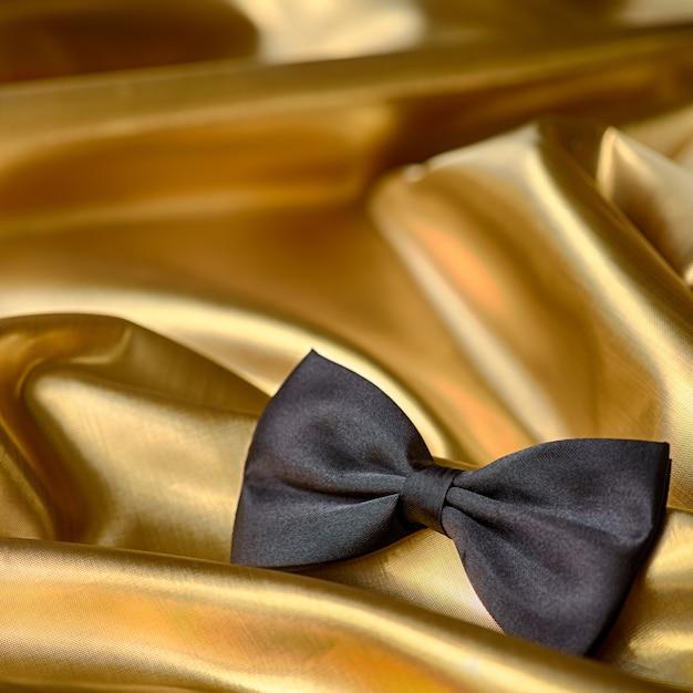 Noeud papillon noir sur fond de tissu doré Photo Premium