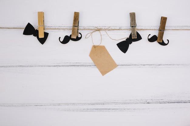 Noeud papillon en papier d'ornement près de la moustache et étiquette sur le fil Photo gratuit