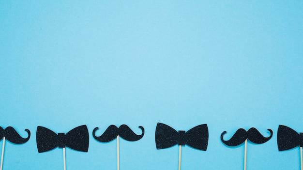 Noeuds papillon et moustaches sur les baguettes Photo gratuit