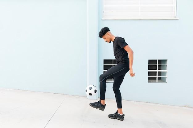 Noir sportif coups de pied de football sous le porche Photo gratuit