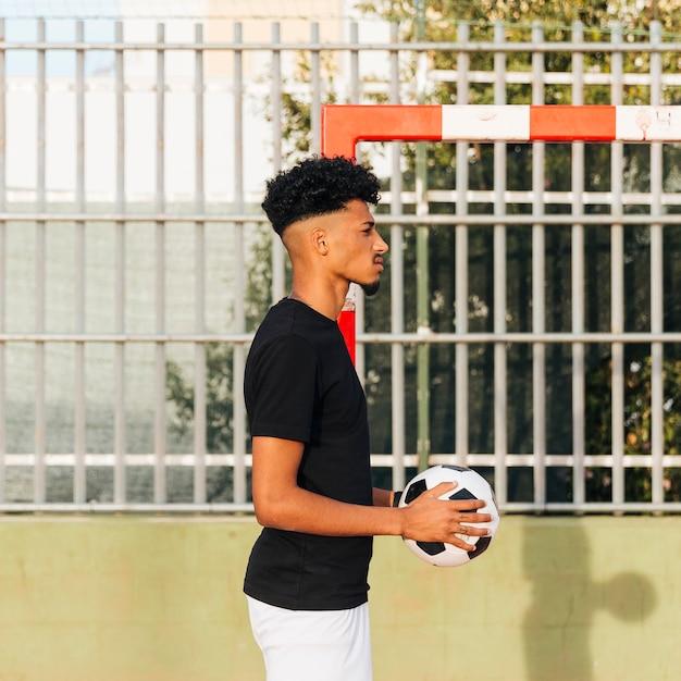 Noir sportif pensif tenant le ballon sur le terrain de sport Photo gratuit