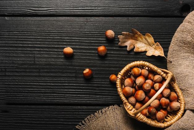 Noisettes et feuilles séchées près de tissu Photo gratuit