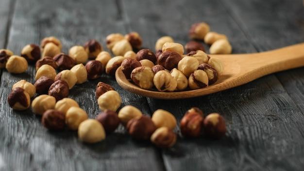 Noisettes Grillées Dans Une Cuillère Sur Une Table En Bois Noire. Préparé Avec La Récolte Des Noisettes. Photo Premium