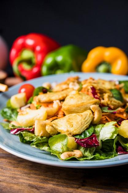 Des noisettes; poulet et légumes d'été sur une assiette sur la table Photo gratuit