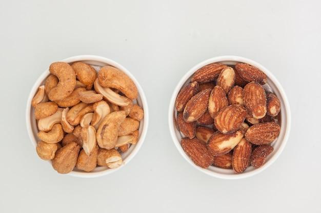 Noix d'amandes et noix de cajou dans une tasse blanche sur fond blanc Photo Premium