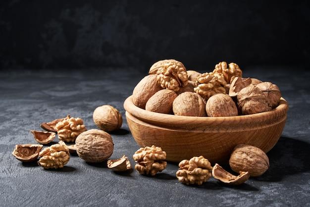 Noix brute dans un bol en bois, gros plan. Photo Premium
