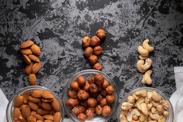 Noix brutes assorties dans une vue de dessus du bol, noix de cajou, amandes, noisettes dans les cuisines Photo Premium