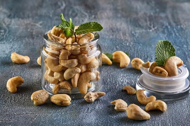 Noix de cajou dans un pot transparent avec des feuilles de menthe sur le dessus Photo Premium