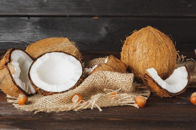 Noix de coco cassée sur une table en bois âgée sombre bouchent Photo Premium