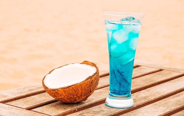 Noix de coco concassée et verre de boisson bleu vif à une table en bois Photo gratuit
