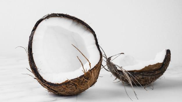 Noix de coco divisée en deux moitiés sur fond blanc Photo gratuit