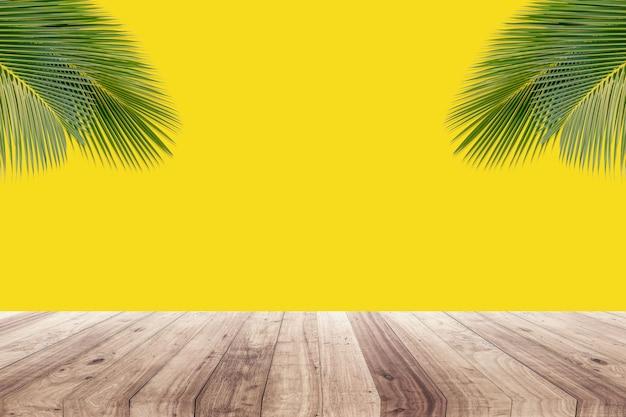 Noix de coco feuilles sur fond jaune pour montrer les produits Photo Premium