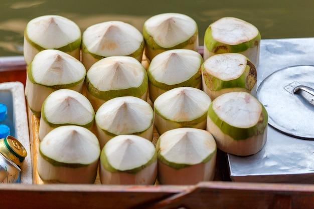 Noix de coco fraîches au marché flottant de damnoen saduak à ratchaburi près de bangkok, thaïlande Photo Premium