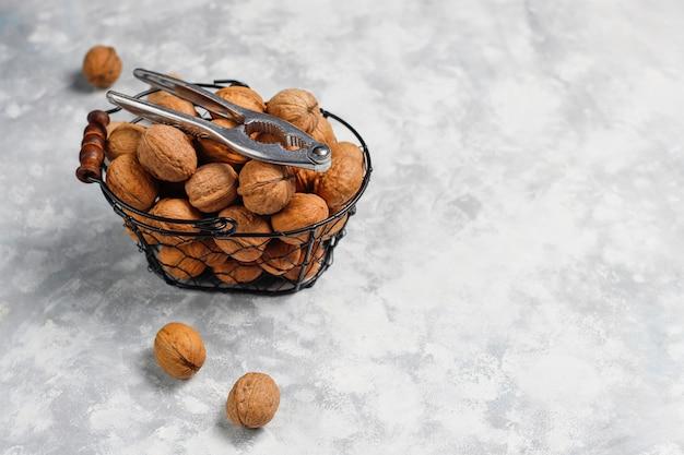 Noix entières en coques dans un panier en métal alimentaire, cerneaux de noix. vue de dessus sur le béton Photo gratuit