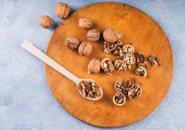 Noix entières et noyau à la cuillère en bois et plateau en toile de fond Photo gratuit