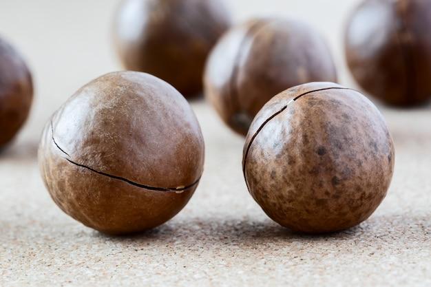 Noix de macadamia entières sur fond marron Photo Premium