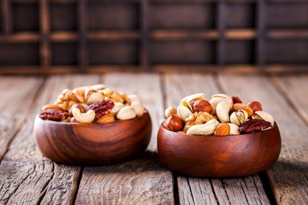 Noix mélangées dans une assiette en bois Photo Premium