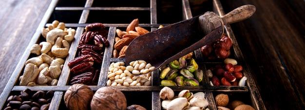 Noix mélangées dans une boîte en bois vintage. assortiment Photo Premium