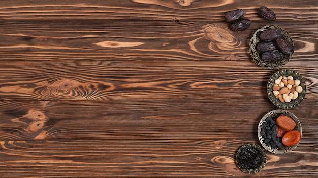 Noix mélangées; dates et fruits secs pour le festival du ramadan sur fond en bois Photo gratuit