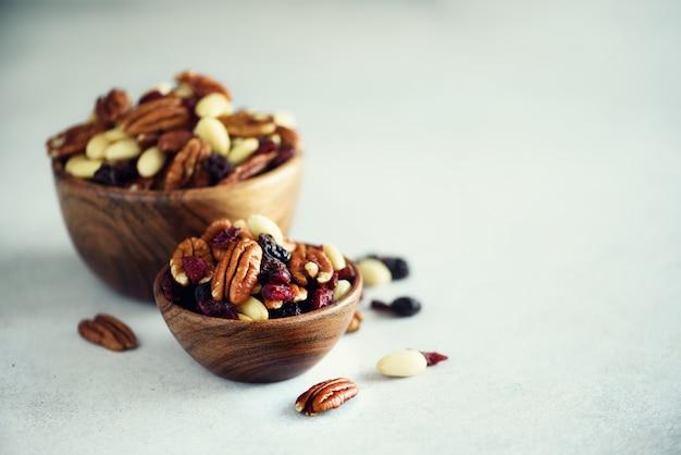 Noix mélangées et raisins secs dans un bol en bois. Photo Premium
