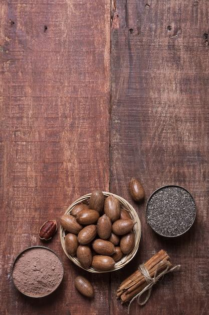 Noix De Pécan, Graines De Chia Et Cacao Dans Des Bols Sur Une Table En Bois Photo Premium