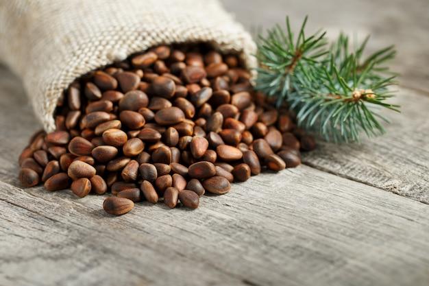 Noix de pin dans un sac de jute avec une branche vert sapin. à la campagne Photo Premium