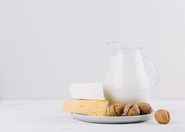 Noix; pot de lait et de fromage sur fond blanc Photo gratuit
