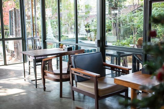 De nombreuses tables et chaises en bois sont situées près des fenêtres de la pièce. Photo Premium