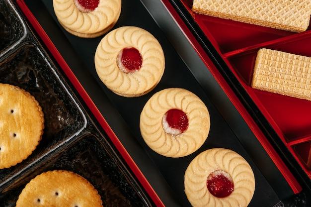 De nombreux biscuits sont joliment disposés dans une assiette puis placés sur une table en bois. Photo gratuit