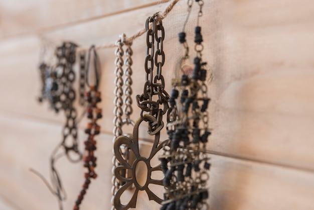 De nombreux bracelets métalliques suspendus à une ficelle contre un mur en bois Photo gratuit