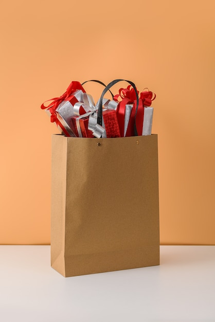 Nombreux coffret cadeau avec ruban rouge dans un sac en papier brun. concepts cadeau du nouvel an ou noël Photo Premium