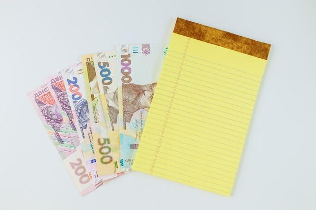 De Nombreux Nouveaux Billets Hryvnia Ukrainienne Dans Le Cahier Jaune Sur Fond Blanc Photo Premium
