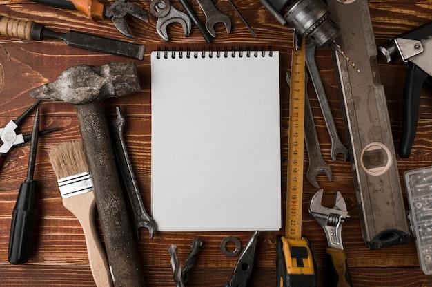 De nombreux outils pratiques et cahier vierge sur une table en bois, vue de dessus Photo Premium